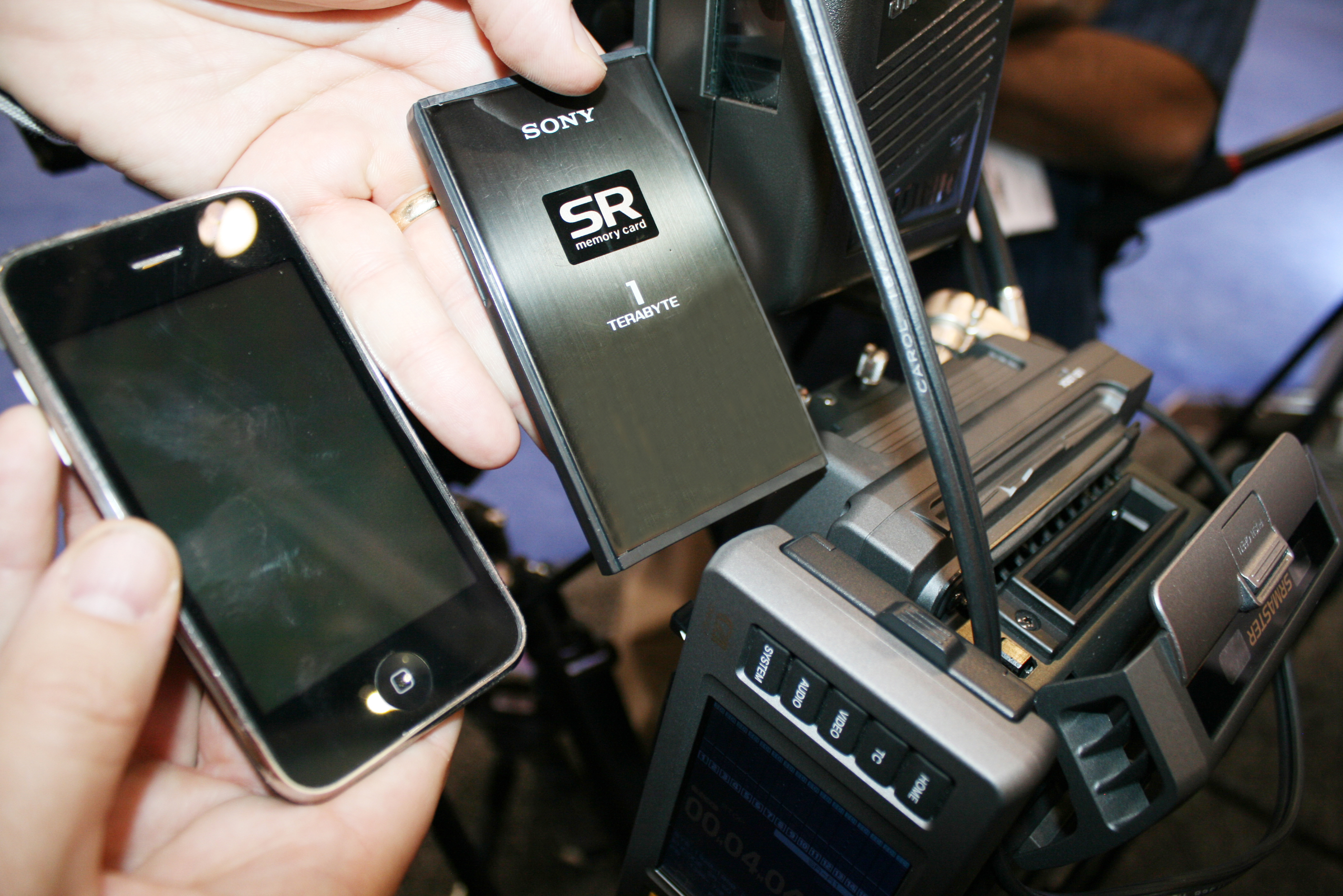 Sony 1TB SRMemory card compared to iPhone. At right is SRMemory companion recorder for Sony PMW-F3.